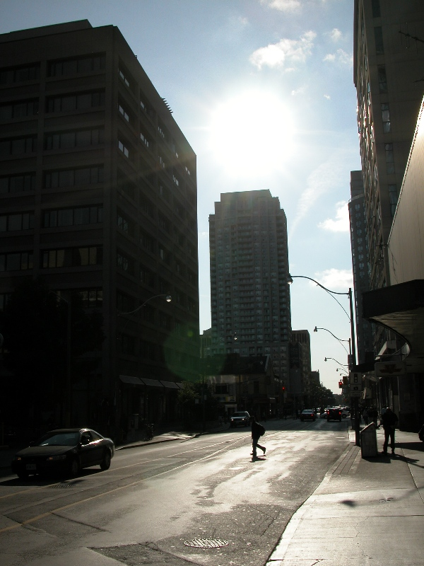 Photo of downtown street flanked by highrise buildings with the sun perched overhead.
